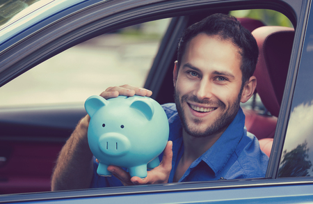 low: Side view happy man sitting inside his new car holding piggy bank Stock Photo