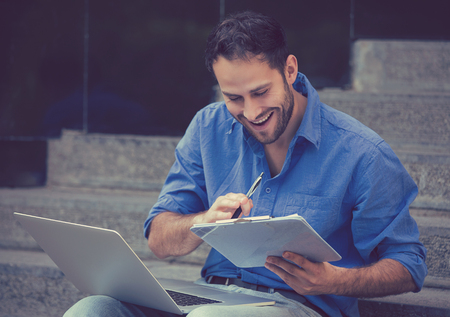 Busy happy man working on laptop outside corporate office Stock Photo