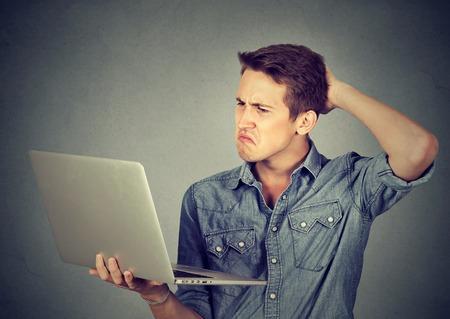 Grappig clueless domme man met problemen met zijn laptop. Ingewikkelde technologie-concept