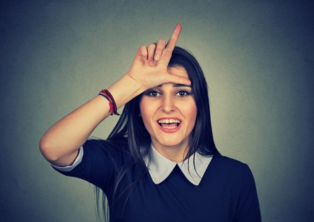 degrade: woman giving loser sign looking at you, making fun isolated on gray wall background Stock Photo