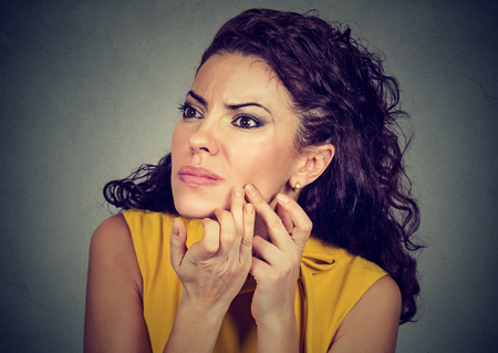 blackhead: Closeup portrait of young woman looking in a mirror squeezing an acne or blackhead on her face. Stock Photo