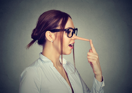 forgery: Woman with long nose isolated on gray wall background. Liar concept. Human face expressions, emotions, feelings