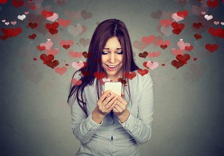Portret mooie jonge vrouw het verzenden van ontvangen van liefde sms tekstbericht op de mobiele telefoon met rode harten vliegen omhoog geïsoleerd op grijze muur achtergrond. menselijke emoties
