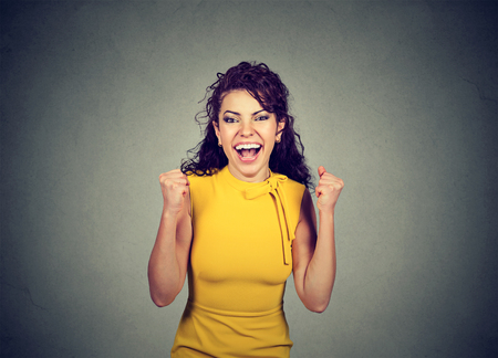jubilate: Successful woman with fists pumped celebrating success isolated on gray wall background. Positive human emotion. Life perception Stock Photo