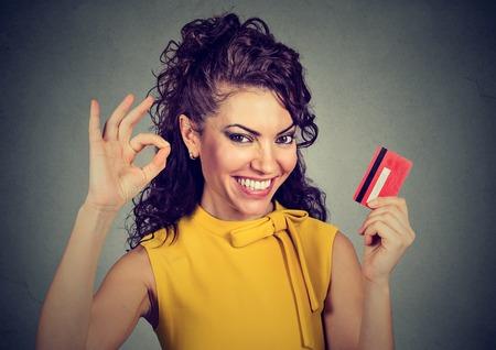 행복 한 여자 확인 기호를 보여주는 신용 카드를 들고