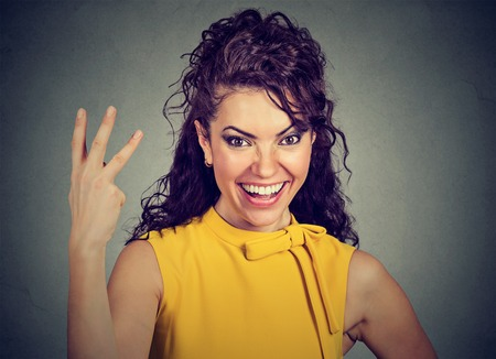 Woman giving a three fingers sign with hand isolated on gray background. Positive emotion feelings