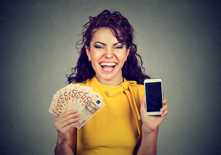 cash money: Happy woman in yellow dress holding mobile phone and euro banknotes cash  Foto de archivo