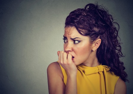 panicky: Closeup portrait young scared nervous woman biting her fingernails craving for something or anxious isolated on gray background. Negative human facial expression feeling
