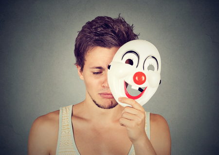 self expression: Young sad man taking off clown mask isolated on gray wall background. Human emotions Stock Photo