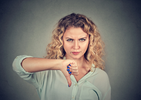 sucks: Woman giving thumb down gesture looking with negative expression and disapproval isolated on gray background