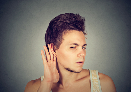 Closeup portrait a man placing hand on ear listening carefully to gossip isolated on gray wall background. Human emotion  Stock Photo