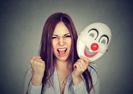 formalities: Portrait angry screaming woman taking off a clown mask expressing happiness isolated on gray wall background. Human emotions feelings