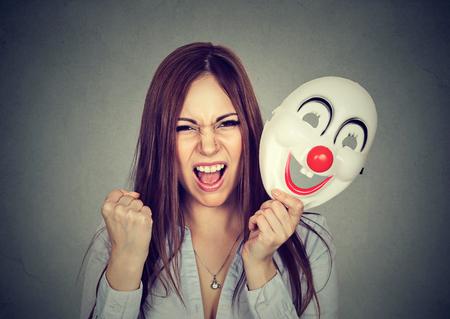 emociones: Retrato mujer gritando enojado quitándose una máscara de payaso que expresa la felicidad aislado en el fondo de la pared gris. Las emociones humanas sentimientos Foto de archivo