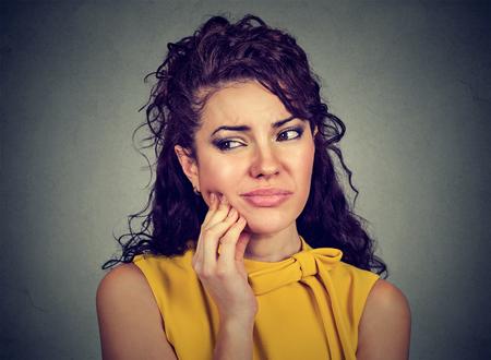 Junge Frau des Nahaufnahmeporträts mit empfindlichem Zahnschmerzkronenproblem, das ungefähr ist, vor Schmerz zu weinen, der Mund mit der Hand lokalisiertem grauem Hintergrund berührt. Negatives Gefühl Gesichtsausdruck Gefühl