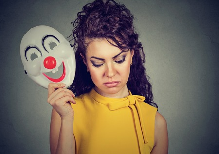 Portrait sad woman taking off clown mask expressing cheerfulness happiness isolated on gray wall background
