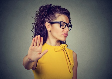 Portrait young angry woman with bad attitude giving talk to hand gesture with palm outward isolated on gray background. Negative human emotion face expression feeling body language