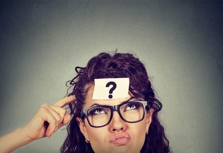 Pensamiento perplejo mujer con signo de interrogación aislado en fondo gris de la pared. Pensativo niña rascarse la cabeza buscando resolver un problema Foto de archivo - 71799902
