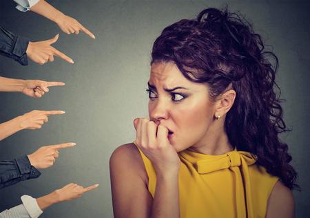 Mujer ansiosa a juzgar por personas diferentes dedos señaló a ella. Concepto de acusación de chica culpable. Las emociones humanas negativas se enfrentan a la sensación de expresión Foto de archivo