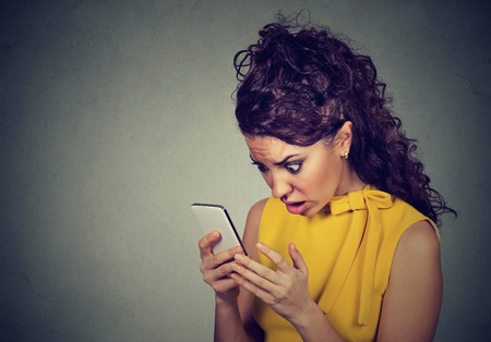 Scared shocked young woman holding cellphone in hands looking at screen with cross face expression at stressful texts and calls isolated on gray background. Negative human emotion