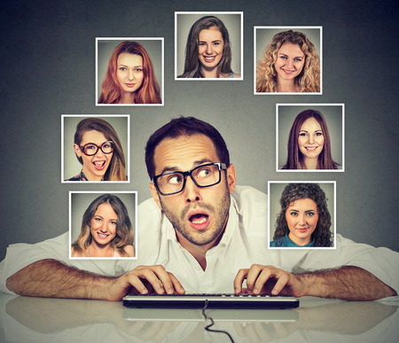 Handsome young man typing on the keyboard wondering thinking which woman he likes loves the most  Stock Photo
