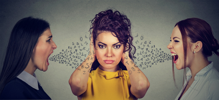 Two angry women screaming at peaceful girl covering her ears with hands ignoring them, alphabet letters coming out of mouth. Anger management emotional intelligence concept Stock Photo