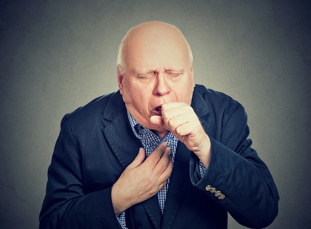 Old man coughing holding fist to mouth isolated on gray background Zdjęcie Seryjne - 73376529