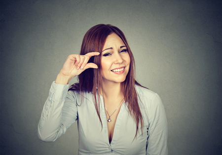 Woman showing small amount size gesture with hand fingers isolated on gray wall background. Human emotion facial expression feelings symbol body language