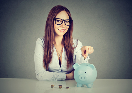 coin bank: Woman inserting coin in a piggy bank