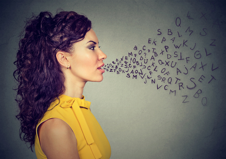 monologue: Woman talking with alphabet letters coming out of her mouth. Communication, information, intelligence concept Stock Photo