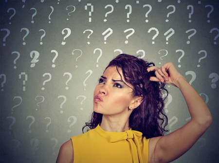 seeks: Portrait confused thinking young woman bewildered scratching her head seeks a solution looking up at many question marks isolated on gray background. Human face expression Stock Photo