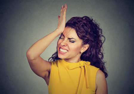 duh: Silly young woman, slapping hand on head having duh moment isolated on gray background. Negative human emotion facial expression feeling, body language, reaction