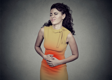 Young woman with hands on stomach having bad aches pain isolated on gray background. Food poisoning, cramps. Negative emotion face expression health problems Фото со стока