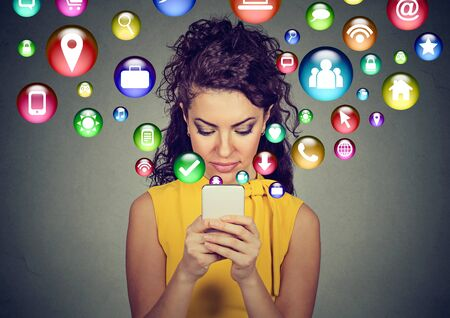 mujer joven feliz usando mensajes de texto en teléfonos inteligentes con los símbolos Uso de medios de comunicación social iconos que vuelan de la pantalla aislados fondo gris
