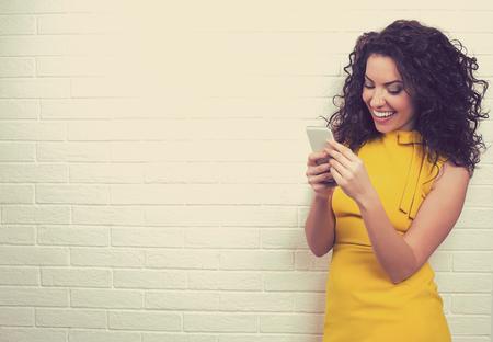 Retrato de mujer atractiva utilizando la conexión de alta velocidad a Internet, enviar mensajes de texto a sus amigos a través de redes sociales en el teléfono inteligente aislados contra la pared de ladrillo Foto de archivo - 73377345