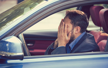 young man sitting inside his car and feeling stressed and upset Banque d'images