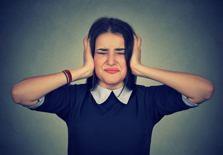 ethnic woman: Stressed woman upset frustrated covering her ears with hands isolated on gray background Stock Photo