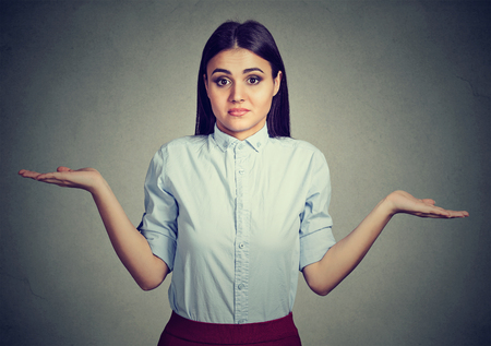 shrugs: Woman with arms out shrugs shoulders so what I dont know isolated on gray wall background. Negative human emotion, facial expression Stock Photo