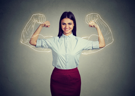 Powerful confident woman flexing her muscles isolated on gray wall background. Human face expressions, emotions