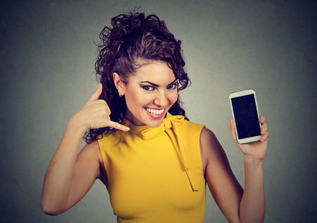 Pretty woman holding mobile phone showing call me hand gesture looking at you camera. Stock Photo