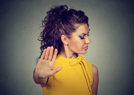 Closeup portrait annoyed angry woman with bad attitude giving talk to hand gesture with palm outward isolated gray wall background. Negative human emotion face expression feeling body language