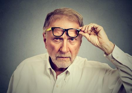 Sceptische senior man met een bril te kijken naar je geïsoleerd op een grijze achtergrond. Menselijke emoties, lichaamstaal