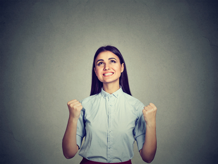 jubilate: Portrait of a successful woman with fists pumped celebrating success isolated on gray wall background. Life perception reaction Stock Photo