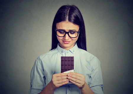 Portrait sad woman tired of diet restrictions craving sweets chocolate bar isolated on gray background. Human emotions. Nutrition concept. Feelings of guilt Stock Photo