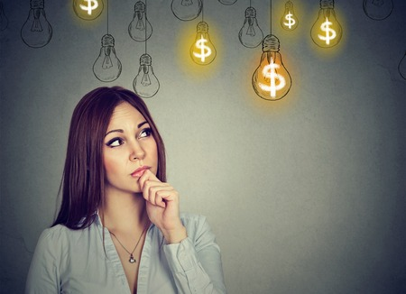 Portrait thinking young woman looking up at dollar idea light bulbs above head isolated on gray wall background