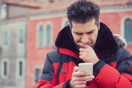 Confused upset man looking at his mobile phone standing outdoors on a city urban street background Stock Photo