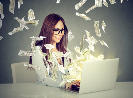 Professional smart young woman using a laptop building online business making money dollar bills cash coming out of computer. Beginner IT entrepreneur success economy concept Stockfoto