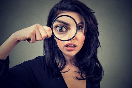 Verraste vrouw die door vergrootglas kijkt dat op grijze muurachtergrond wordt geïsoleerd. Stockfoto