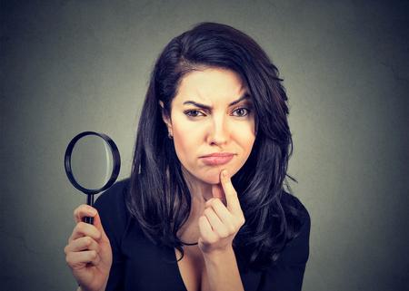 Jeune femme curieuse avec une loupe isolée sur un fond de mur gris. Banque d'images - 74969171