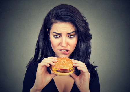 craving: Young woman craving a tasty burger