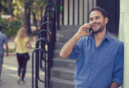 outdoor outside: Man talking on phone. Casual urban professional entrepreneur using smartphone smiling happy outside office building. Outdoor portrait of modern young guy with mobile in the street Stock Photo